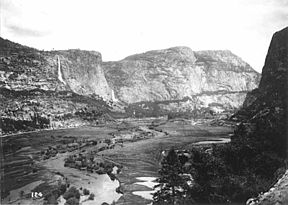 This photograph, taken in the early 1900s before the O'Shaughnessy Dam was constructed, shows the Hetch Hetchy Valley and the Tuolumne River, looking east.