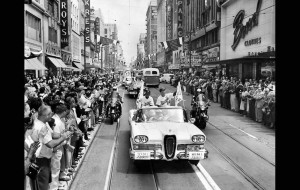 Spectators line Broadway as Dodgers manager Walter Alston, right, and coach Charlie Dressen ride in a caravan to their first game at the Coliseum.
