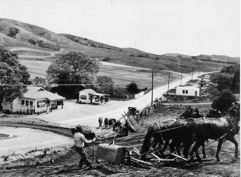 "Mule-drawn ""Fresno Grader"" working near Marshall store and gas station on Orinda Way. The first Orinda fire house is on the right."