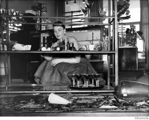 Margaret Gaines began to tidy up the debris of broken glassware at a Stonestown shop following the earthquake in March 1957. Photo courtesy San Francisco Chronicle.